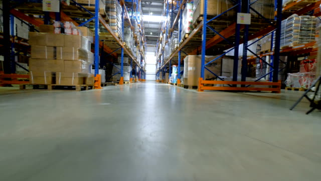 Storage, warehouse indoors. Camera goes along shelfs, racks. 4K. video