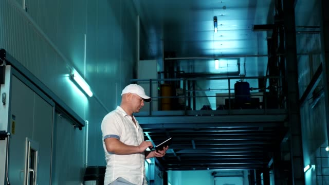storage. warehouse. male employee with digital tablet works in warehouse. walks past special large refrigerating chambers. crop storage in agriculture. apple business video