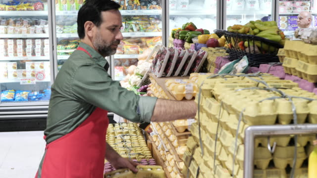 store or isle manager in supermarket working on fresh fruit and vegetables department - супермаркет стоковые видео и кадры b-roll
