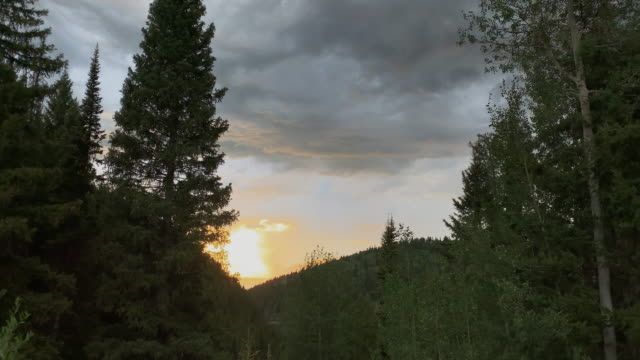 storm clouds and a sunset over forested mountains close to targhee village near alta, wyoming - conifera video stock e b–roll
