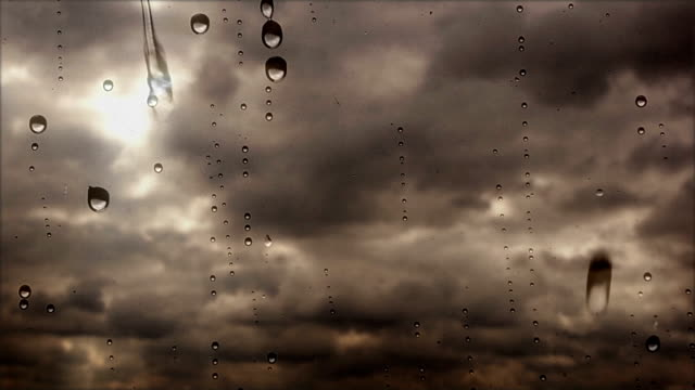 stockvideo's en b-roll-footage met close-up van storm wolken vliegen snel via het regenachtige venster - regen zon