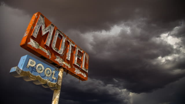 stockvideo's en b-roll-footage met storm gathering over rustic motel sign - time lapse - arizona highway signs