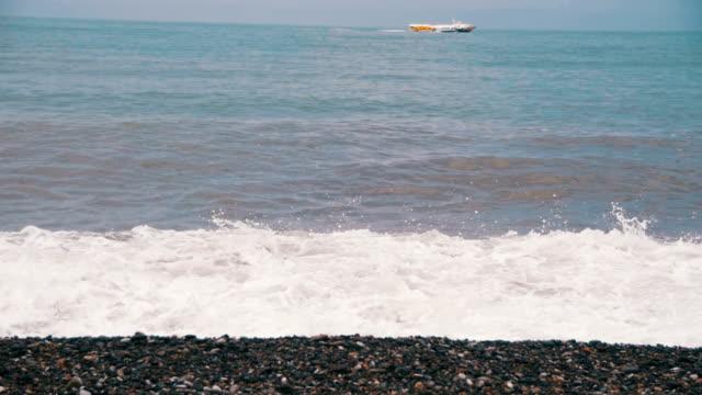 vídeos de stock e filmes b-roll de storm on the sea. the waves are rolling on a pebble stone beach. slow motion - transatlântico