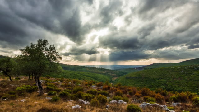 A stormy sunset with sunlight rays crossing the clouds and lighting a valley in Casmilo, Serra do Sicó, Portugal - Timelapse