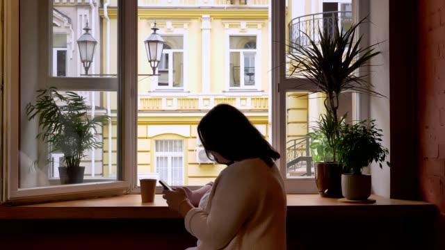 stout caucasian frauen scrollen auf handy in der nähe von fenster im café mit papierbecher - kräftig gebaut stock-videos und b-roll-filmmaterial