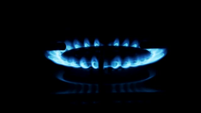 Stove top burner igniting into a blue cooking flame