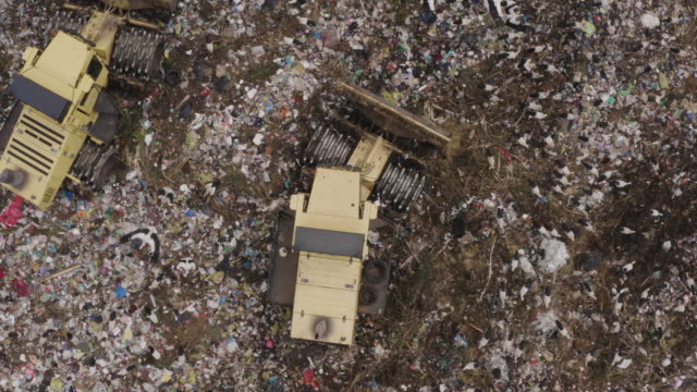 4K straight down aerial zoom in view of European White Storks scavenging for food on a landfill dump site while bulldozers work amongst them