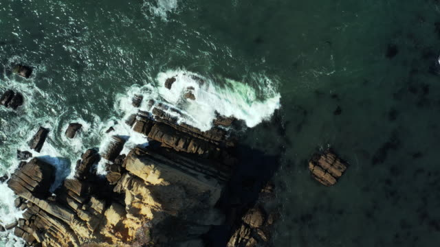 Straight Down Arial View Of Waves Crashing Against Rocks In Mendocino A top down drone shot of the ocean water hitting the rocks near the shore. The water turns white and foamy from being agitated by the rocks. b roll stock videos & royalty-free footage