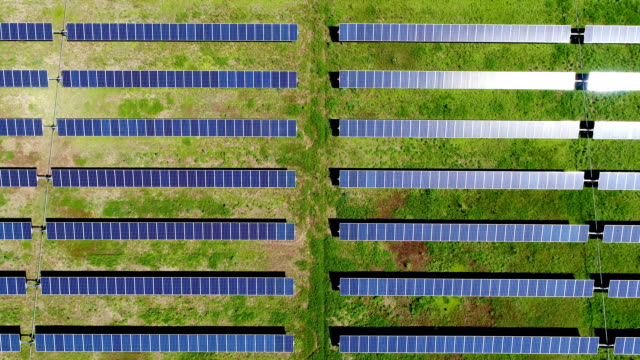 vídeos de stock e filmes b-roll de straight down straight rows solar panel power plant providing clean renewable energy to help fight against climate change and create jobs - energia solar