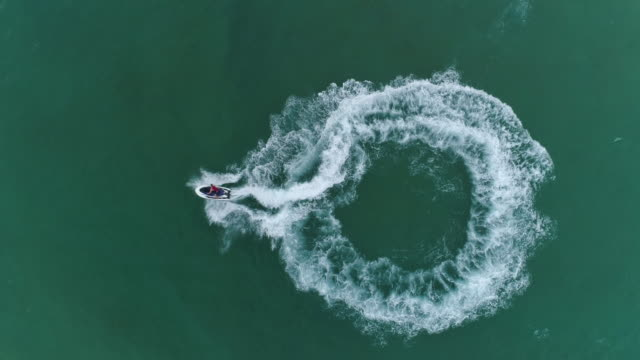 4K straight down zoom out spectacular aerial view of man having fun riding a personal watercraft in the ocean making a figure of eight pattern, Mozambique