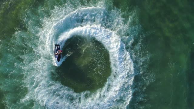 4k gerade nach unten zoom aus spektakulären luftbild des mannes spaßam reiten ein persönliches wasserfahrzeug im ozean machen ein kreisförmiges muster, mosambik - kreis stock-videos und b-roll-filmmaterial