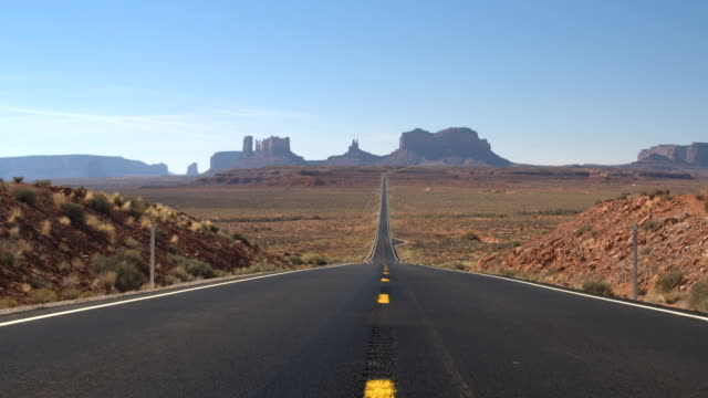 LOW ANGLE VIEW: Straight empty road leading to iconic Monument Valley Utah USA video