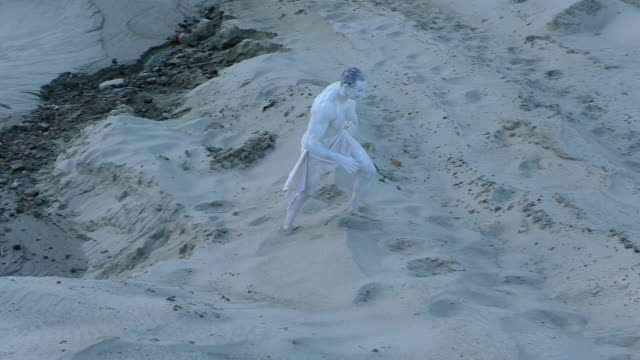 Strange man steps on the sand. Strange man is walking along the sand, he is an alien. greasepaint stock videos & royalty-free footage