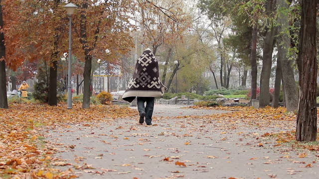 Strange man wandering in city park covered with blanket, mentally ill person video