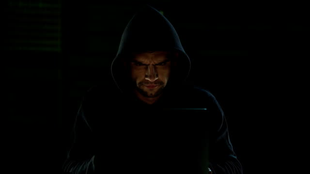 Stranger in dark sweatshirt with hood intently typing, gazing at monitor screen Stranger in dark sweatshirt with hood intently typing, gazing at monitor screen identity theft stock videos & royalty-free footage