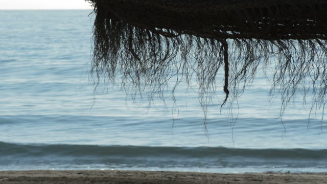 Straw beach umbrella with sea waves breaking on the shore on a sunny morning video