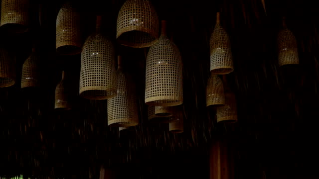 Straw decorative chandeliers are hanging under the palm leaves roof. video