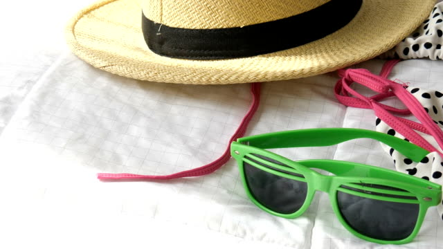 Straw hat, green sun glasses and bikini on white bed, preparing for backpack and holiday. Straw hat, green sun glasses and bikini on white bed, preparing for backpack and holiday. swimwear stock videos & royalty-free footage