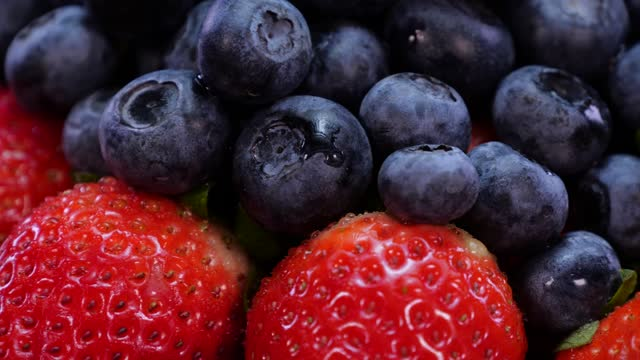 vídeos de stock e filmes b-roll de strawberries and blueberries rotating on a black background close up. fresh, organic vibrant red strawberry and blueberry in 4k. raw vegan summer snack. - morango