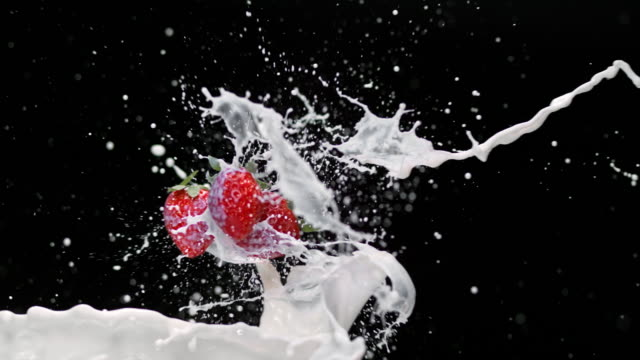 SLO MO Strawberries being splashed by milk in the air video