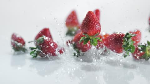 vidéos et rushes de slo missouri ld fraises couvertes de rebondir sur une surface de l'eau - fraise