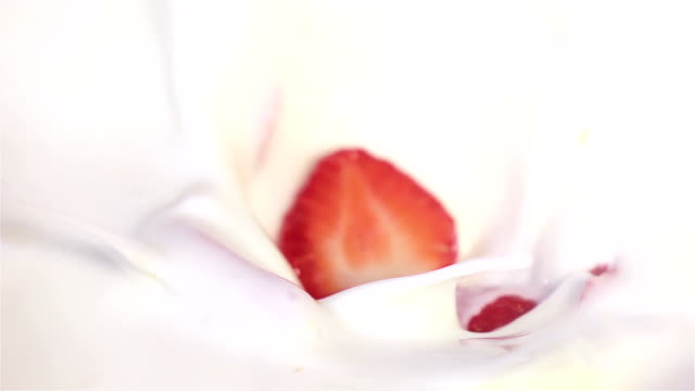 Strawberries falling into yogurt in real slow motion video