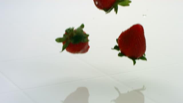 Strawberries splashing, slow motion video