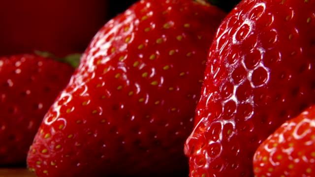 vídeos de stock e filmes b-roll de strawberries with drop of water flowing over surface - morango