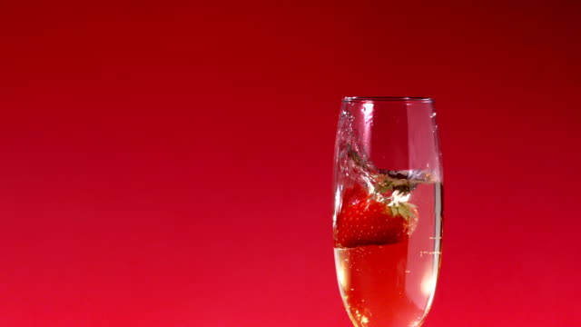 erdbeeren fallen in flöte champagner - champagner toasts stock-videos und b-roll-filmmaterial