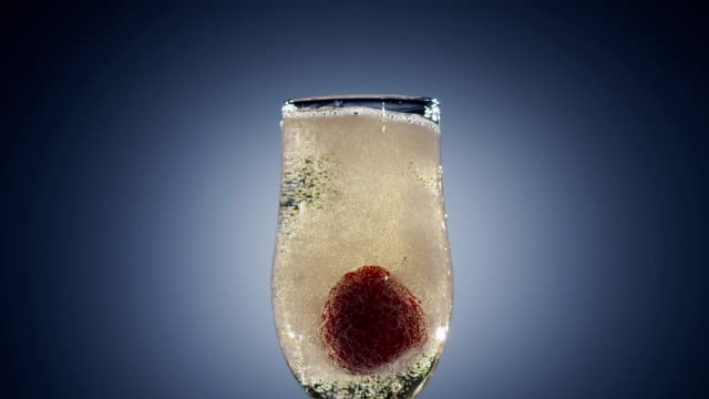 Strawberry falling into full glass of champagne wine. Slow motion video