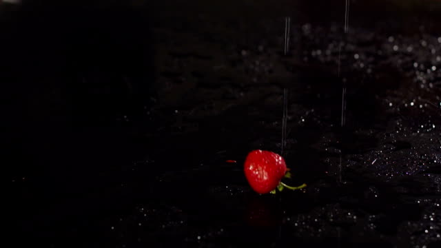 Strawberry falling on wet black surface, slow mo. video