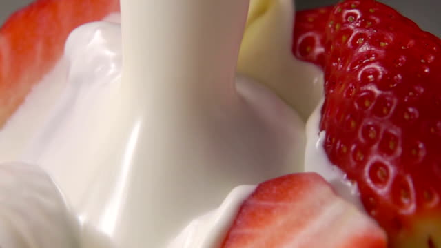 Strawberry halves fall into milk
