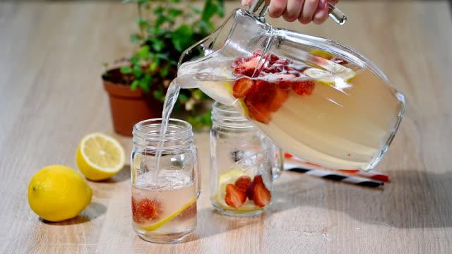 vídeos de stock e filmes b-roll de strawberry lemonade with ice in mason jar on a wooden table. - limonada tradicional