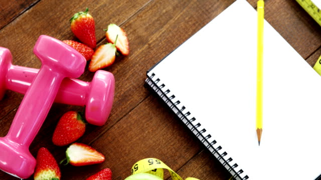 Strawberry, measuring tape, dumbbells and spiral notebook on table video