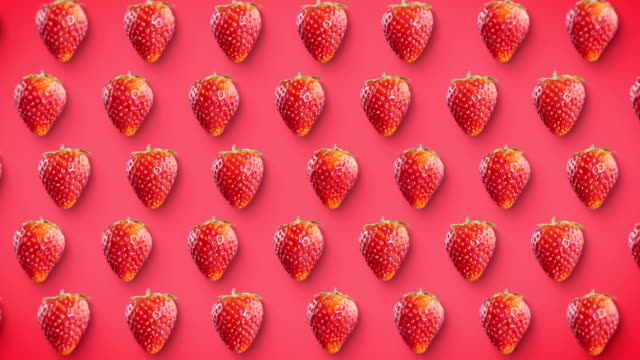vídeos de stock e filmes b-roll de strawberry rotating on pink background looped, stop motion - strawberry