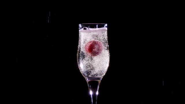 strawberry splash in ein champagnerglas.   zeitlupe motion - champagner toasts stock-videos und b-roll-filmmaterial