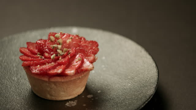 Strawberry tarts with custard - black background video