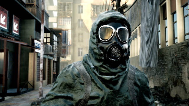 A stray man in military protective clothing and a gas mask is walking through the ruined city. The concept of a post-Apocalyptic world after a nuclear war.