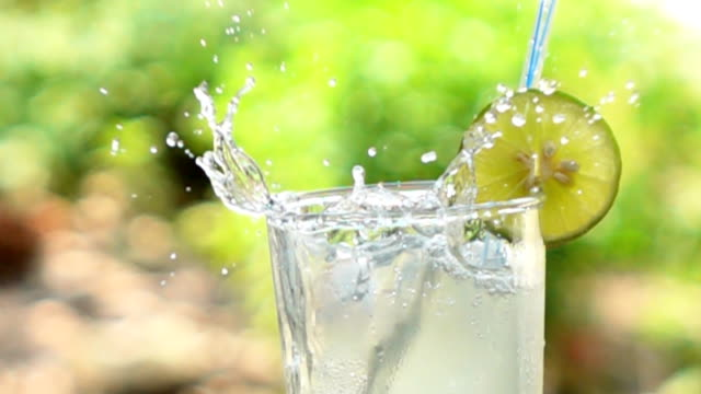 Stream of Lemon Juice. Ice cubes falling into a glass,Slow motion video