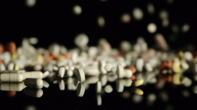 SLOW: Stream of pills  and capsules fall in the darkness