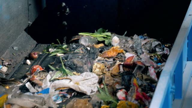 Video Stream of wastes is falling from the conveyor belt. Environmental pollution concept.