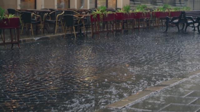 stream of water are flowing through the pavement in rainy weather. - terrazza video stock e b–roll