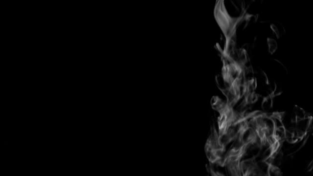 Stream of white smoke coming from the top down on a black background video