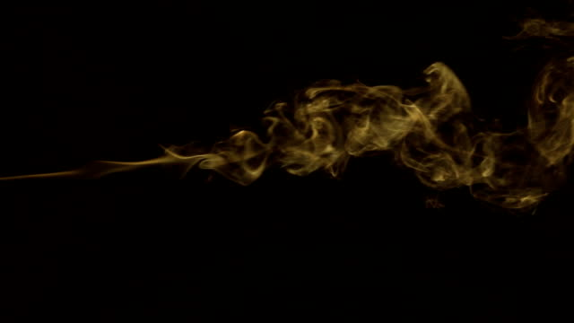 Stream of yellow smoke turning into smoke puffs on a black background video