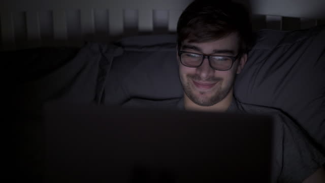 Streaming video on a digital tablet in bed, wide. Young man in 20s using a laptop or digital tablet at night, his face lit by the screen. He could be watching tv or surfing the net. Pan from right to left. 4k stock video. watching tv stock videos & royalty-free footage