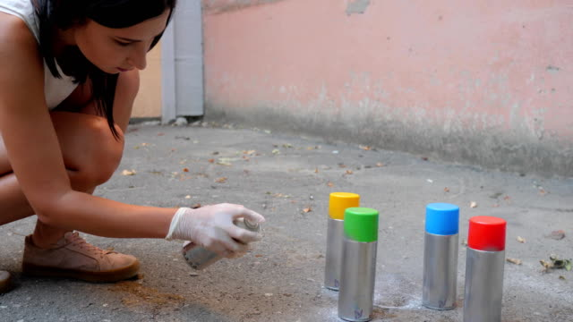 street artist, close-up spray cans in different colors, young woman hands with aerosol paint in slow motion