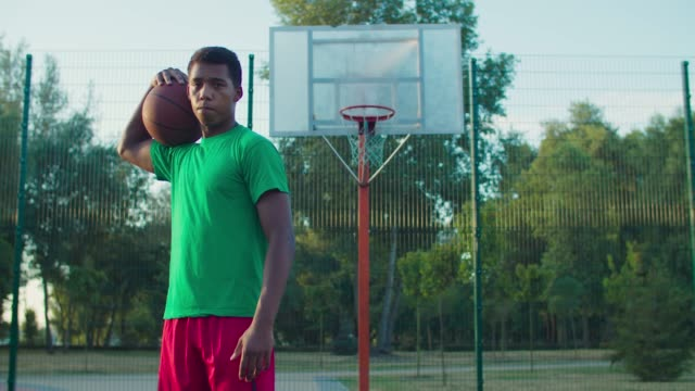 Street basketball player on outdoor court at dawn