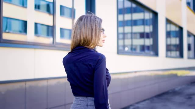 vídeos de stock, filmes e b-roll de rua. edifícios do centro de negócios. um jovem trabalhador se apressa para trabalhar. a mulher está vestida com um vestido de bacalhau - saia