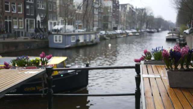 street cafe decorated flowers Cafe on the street of Amsterdam. Panoramic shot on tables decorated colorful spring flowers in pot. View on canal and traditional dutch buildings at blurred background architectural column stock videos & royalty-free footage