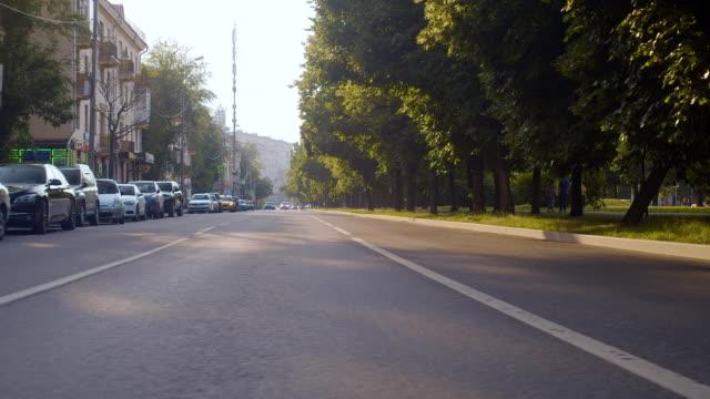 gatu korsningen. rörliga bilar - walking home sunset street bildbanksvideor och videomaterial från bakom kulisserna